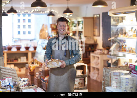 Portrait Of Smiling Male Owner Of Delicatessen Shop Wearing Apron Holding Loaf Of Bread - Stock Image