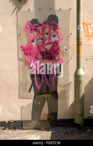 Graffiti tags sprayed on the plastic screen covering the famous Banksy 'Kissing Coppers' graffiti of two - Stock Image