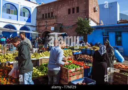 Chefchaouen, Morocco : A young tourist shops for fruit and vegetables at Plaza Bab Suk market square, in the blue-washed medina old town. - Stock Image