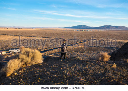 Lifestyle portrait of a six year old boy on the top of a cliff at Fort Rock State Park in South Central Oregon. - Stock Image