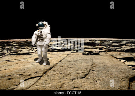 An astronaut surveys his situation after being marooned on a barren planet. The blackness of deep space is the background. - Stock Image