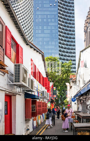Singapore - 22nd December 2018: Tourists in Haji lane with modern office block in the background, This is in the Kampong Glam area - Stock Image
