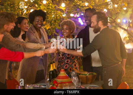 Happy friends toasting wine glasses at dinner garden party - Stock Image