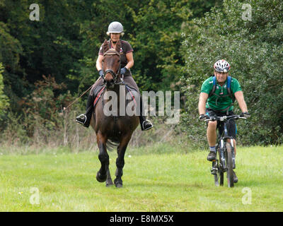 Woman on horse riding with man on a mountain bike, Chettle, Dorset, UK - Stock Image