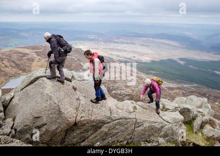 Three hikers scrambling up hill over rocks on Carnedd Moel Siabod Daear Ddu east ridge in mountains of Snowdonia National Park Wales UK - Stock Image