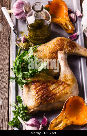 Grilled chicken legs served with roasted pumpkin, pesto sauce and fresh parsley on rustic wooden table, meat and vegetables roast dinner - Stock Image