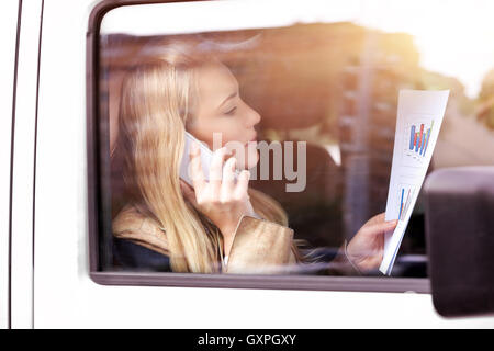 Serious business woman going to work, analyzing graphics and discussing it on the phone from the car - Stock Image