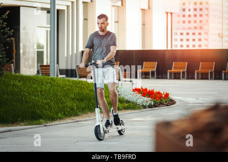 Attractive man riding electric kick scooter next to modern buildings or commercial centres. Man is on foreground, modern cityscape is on background. - Stock Image