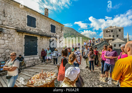 Tourists crowd the Mostar Bridge in the medieval city of Mostar, Bosnia as local Bosnians sell souvenirs and two men prepare to dive - Stock Image