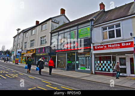 A row of traditional shops in the town centre of Bridgend, S.Wales. Shoppers walking along street with shopping bags. - Stock Image