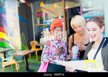Young women friends with map outside smoothie shop - Stock Image