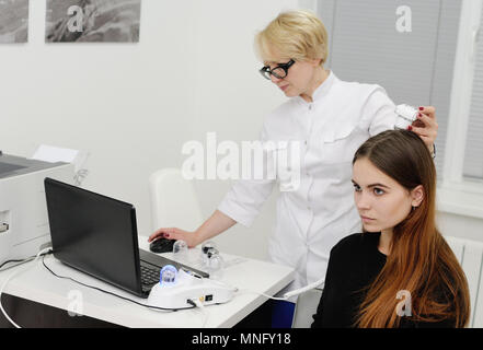 dermatologist examines a patient woman hair using a special device - Stock Image