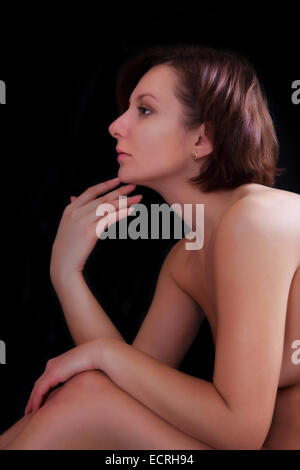 Beautiful young woman on a dark background in profile - Stock Image