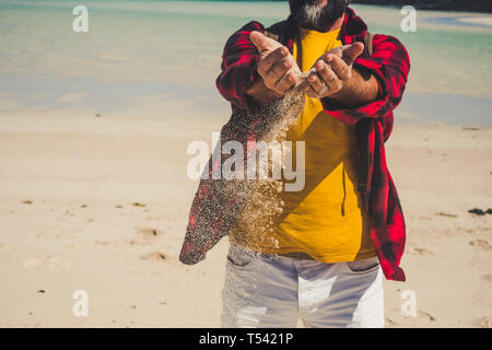 Close u view of unrecognizable caucasian tourist man playing with the sand at the beach durint tropical vacation - adult people enjoy the nature in su - Stock Image
