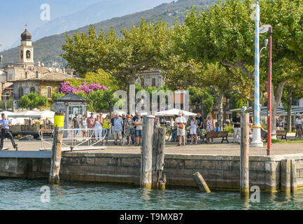 TORRI DEL BENACO, LAKE GARDA, ITALY - SEPTEMBER 2018: People waiting for a ferry to arrive in Torri del Benaco on Lake Garda. - Stock Image