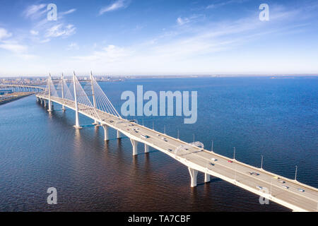 Traffic on the elevated highway over sea in Saint Petersburg, Russia aerial view. Landscape with bridge, cloudy sky and calm sea - Stock Image