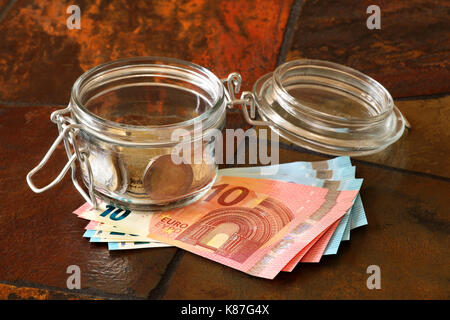 Euro coins in a jar with Euro banknotes underneath; shown on a tiled table top - Stock Image