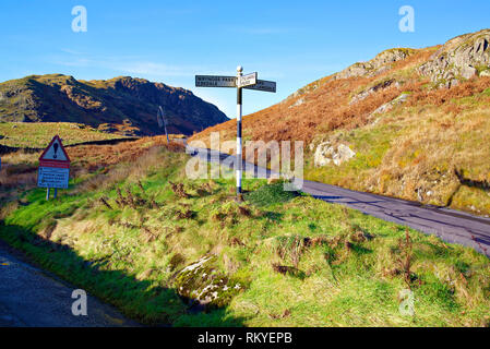 A view of road signs in the hilly landscape of the English Lake District. - Stock Image