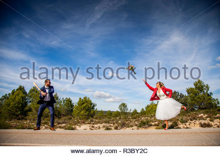 Bride throws her bouquet while groom prepares to hit him with a baseball bat - Stock Image