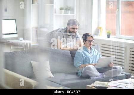 Young man looking at display of laptop held by his wife while both looking through on.line travel offers - Stock Image