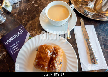 A morning snack at Betty's café a cup of tea and a Pain au Chocolate with a visitors Visit Harrogate brochure on the table - Stock Image