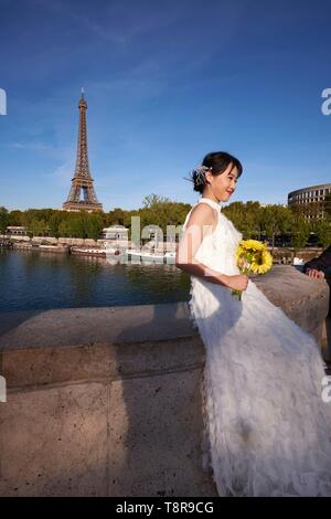 France, Paris, area listed as World Heritage by UNESCO, photo of an asian bride in front of the Eiffel Tower from Bir Hakeim Bridge - Stock Image