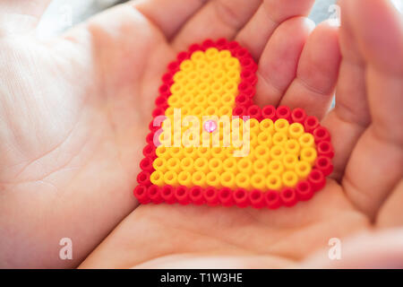 Two hands holding a heart shape. - Stock Image