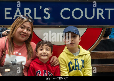 A mother and her young sons pose together in front of a sign at Earl's Court London Underground Station. - Stock Image