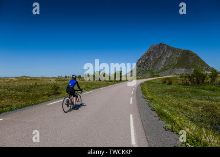 Female cyclist in Gimsoya, Lofoten Islands, Norway - Stock Image