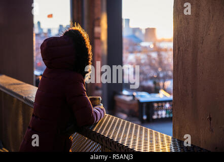 Woman wearing fur hoodie drinking coffee and watching sunset from New York Highline - Stock Image