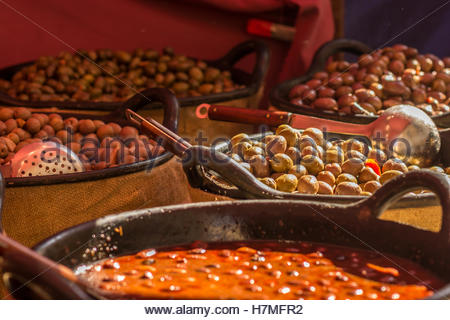 Olives of different flavors in large basins in healthy food market in Spain. - Stock Image