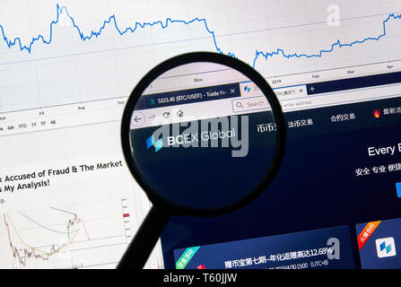 MONTREAL, CANADA - APRIL 26, 2019: BCEX Global cryptocurrency digital assets exchange logo and home page on a laptop screen under magnifying glass. - Stock Image