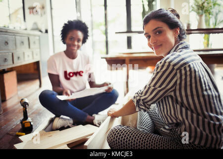 Portrait smiling, confident women with instructions assembling furniture - Stock Image