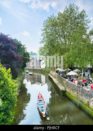 25 May 2018: Totnes Devon UK - Trees and people at a restaurant beside the River Dart. - Stock Image