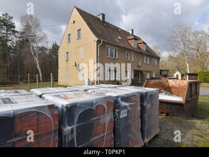 Alwine, Germany. 19th Mar, 2019. Several pallets with roof tiles and a container for building rubble stand in front of a dilapidated apartment building in the small village of Alwine, which belongs to the Domsdorf district of the town of Uebigau-Wahrenbrück in the Elbe-Elster district. (to 'Alwine was auctioned off a year ago') Credit: Patrick Pleul/dpa-Zentralbild/ZB/dpa/Alamy Live News - Stock Image