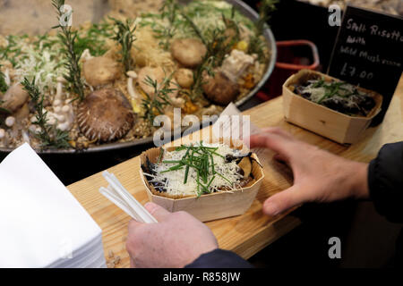 A person customer buying wild mushroom spelt risotto at a Borough Market Christmas food stall in Southwark, South London England UK  KATHY DEWITT - Stock Image