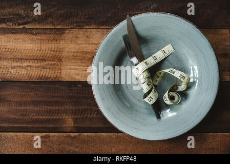 Fork and knife tied up by a measuring tape in a plate on a wooden table. concept of dieting and weight management - Stock Image