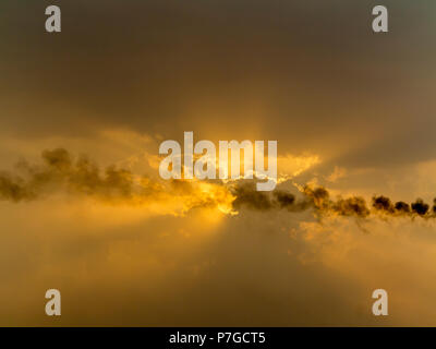 Sunset on the river Nile Egypt in an industrial area with pollution increasing the dramatic orange colours in the clouds - Stock Image
