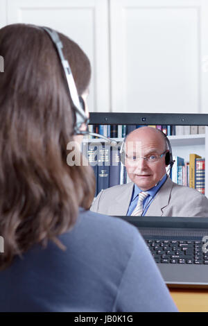 Woman with headset at her desk in front of her laptop having an online chat with her elderly tutor, copy or text - Stock Image