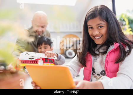 Portrait happy girl using digital tablet - Stock Image