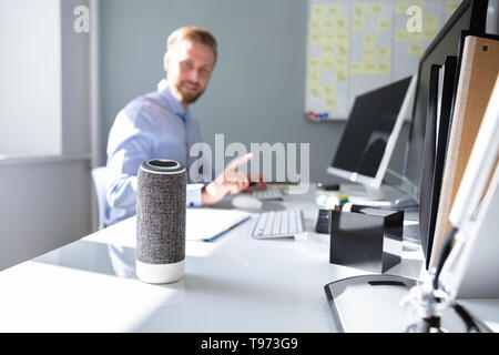 Close-up Of Voice Assistant In Front Of Businessman Working At Desk - Stock Image