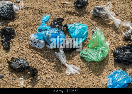 Close-up of discarded colourful plastic dog poop bags in sandy public dog toilet area in city park - Stock Image