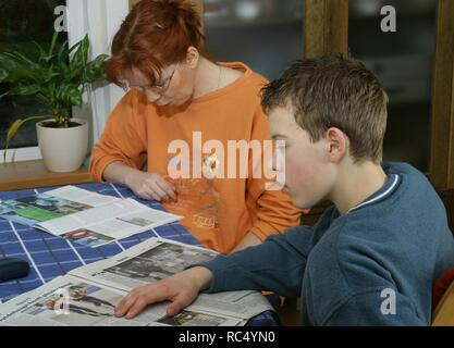 Mother and teenage son at the tab;le reading a magazine and a newspaper in the 2000s - Stock Image