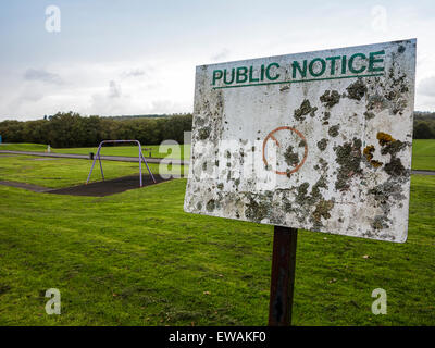 A cryptic notice in a Welsh public park, so old that it has become encrusted with lichen and all the information - Stock Image