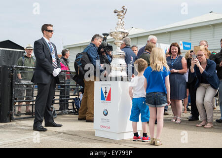 Portsmouth, UK. 23rd July 2015. Members of the general public pose with the America's Cup in-front of HMS Warrior - Stock Image