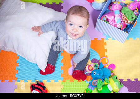7 months baby boy sitting over puzzle play mat. Learning to sit up concept - Stock Image