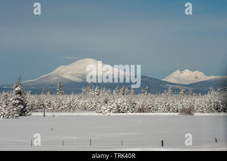 Oregon volcanoes Mt. Bachelor (L) and Broken Top (R) as seen from US Hwy 97 in LaPine, Oregon after a good snow. - Stock Image