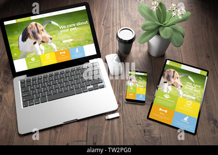 3d rendering of three devices with pet responsive website on screen on wooden desktop top view - Stock Image