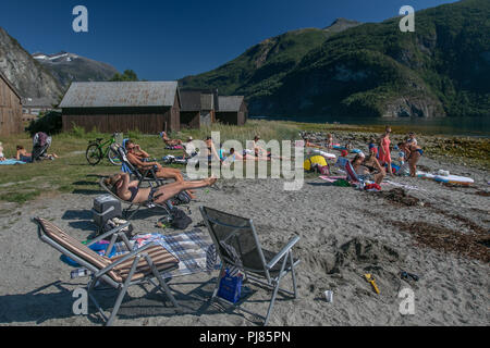 Norway, July 26, 2018: People are sunbathing on a fjord beach on a hot summer day. - Stock Image