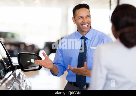 friendly vehicle dealer showing young woman new car - Stock Image
